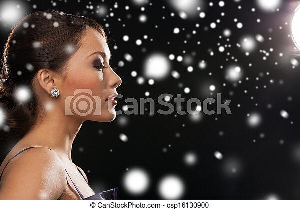 woman in evening dress wearing diamond earrings - csp16130900