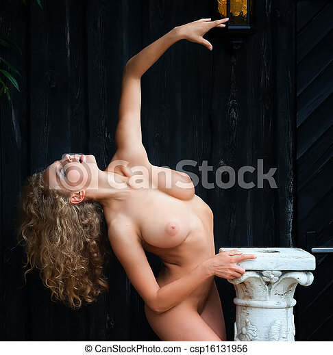 nude woman posing near the old country house