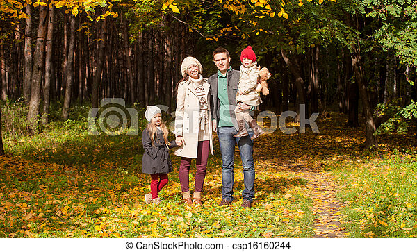 Young parents with their wonderful beautiful daughter walk in autumn park on a sunny warm day - csp16160244