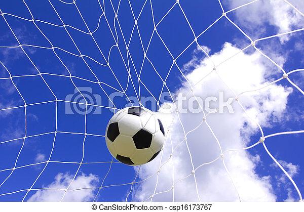 Soccer ball in goal net over blue sky background
