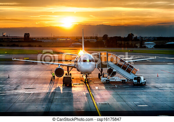 Airplane near the terminal in an airport at the sunset - csp16175847