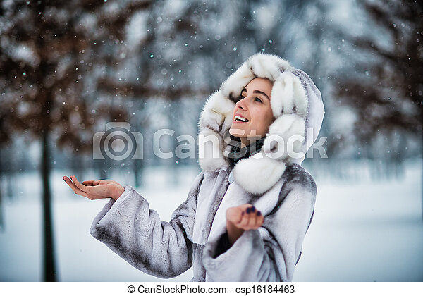 Happy woman in winter park have fun with a snow - csp16184463