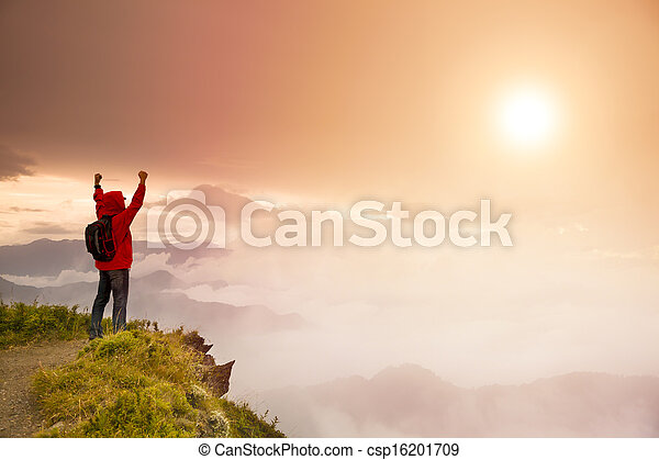 Young man with backpack standing  on top of  mountain watching the sunrise - csp16201709