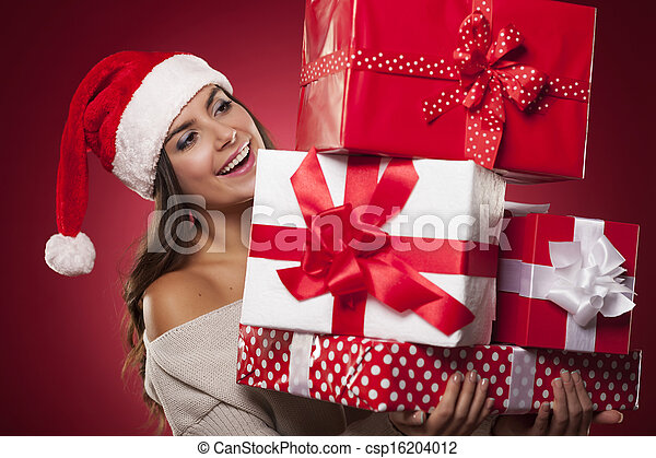 Cute young woman wearing santa hat holding christmas gifts - csp16204012
