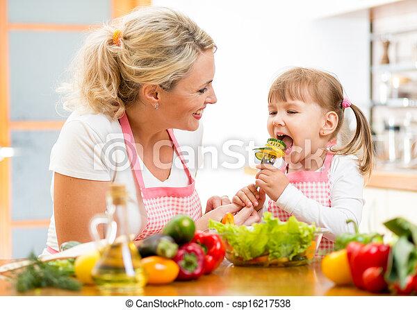 mother feeding kid daughter vegetables in kitchen - csp16217538
