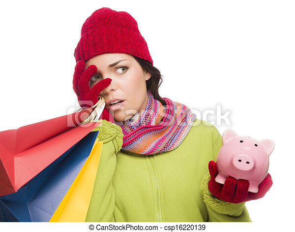 Concerned Expressive Mixed Race Woman Wearing Winter Clothing Holding Shopping Bags and Piggybank Isolated on White Background. - csp16220139