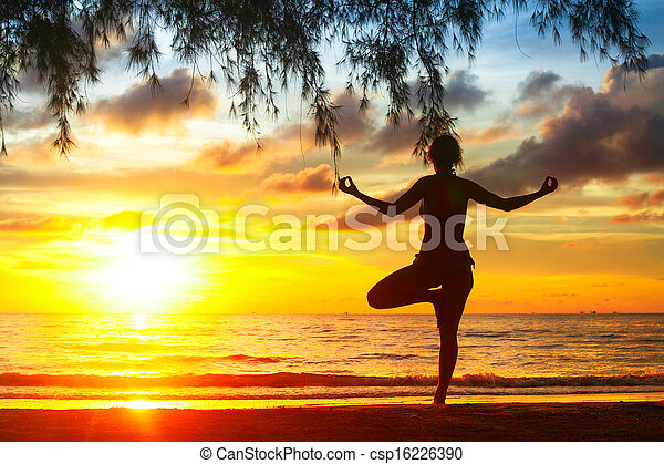 Silhouette of young woman practicing yoga on the beach at sunset. - csp16226390