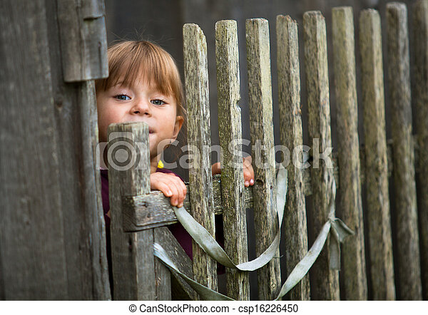 Beautiful child standing near vintage rural fence. - csp16226450