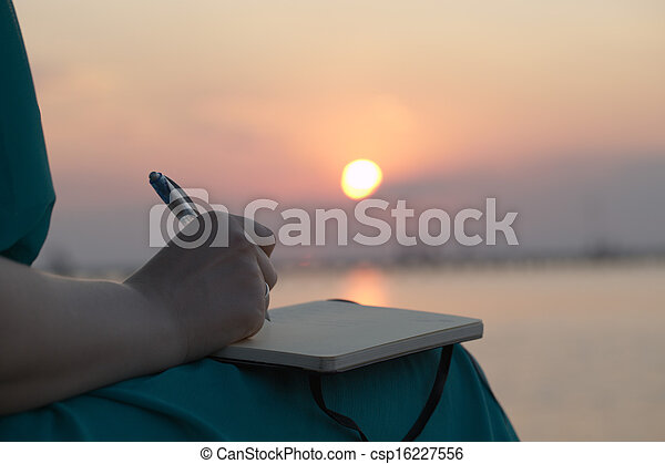 Woman writing in her diary at sunset - csp16227556