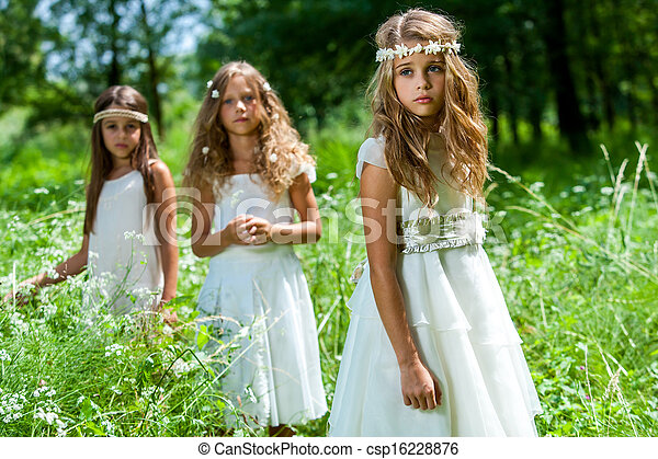 Three girls wearing white dresses in woods. - csp16228876