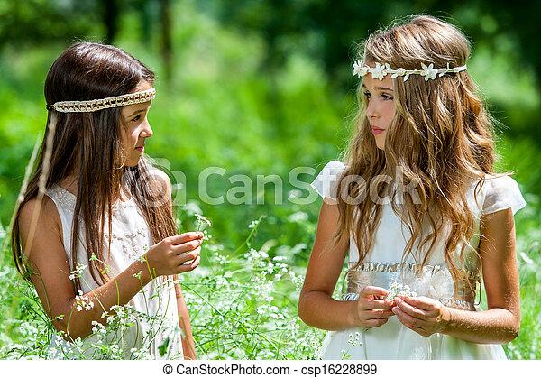 Two girls standing in flower field. - csp16228899