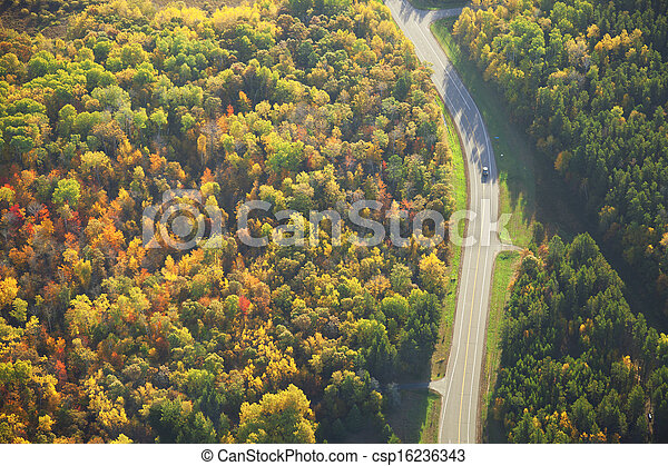 Aerial view of road curving through woods in fall color - csp16236343