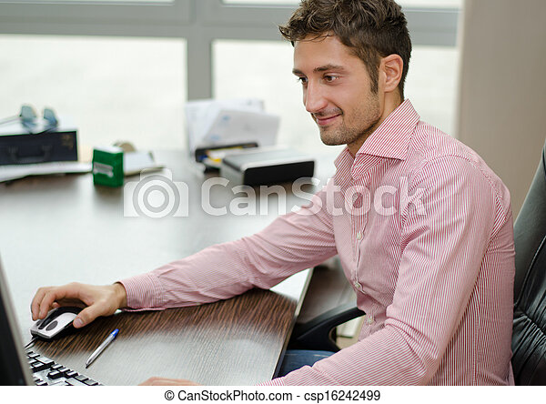 Handsome, happy office worker smiling while using computer - csp16242499