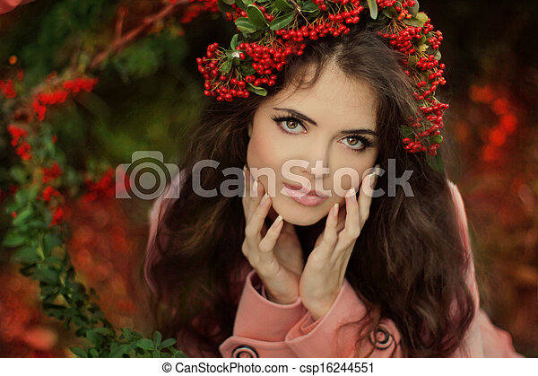 Autumn Girl Portrait. Beautiful young brunette Woman in red berries chaplet at the autumn park. Outdoor shot. - csp16244551