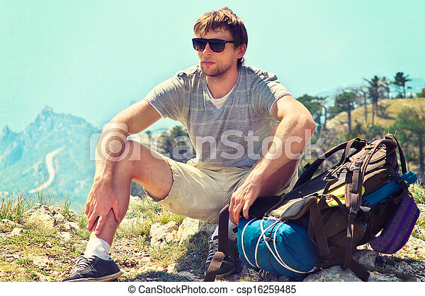 Young Man Traveler with backpack relaxing on Mountain summit rocky cliff  with aerial view of Sea on background Hiking and Healthy Lifestyle concept - csp16259485