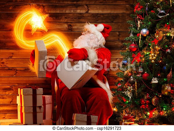 Santa Claus in wooden home interior holding gift box with magic star flying out of it - csp16291723