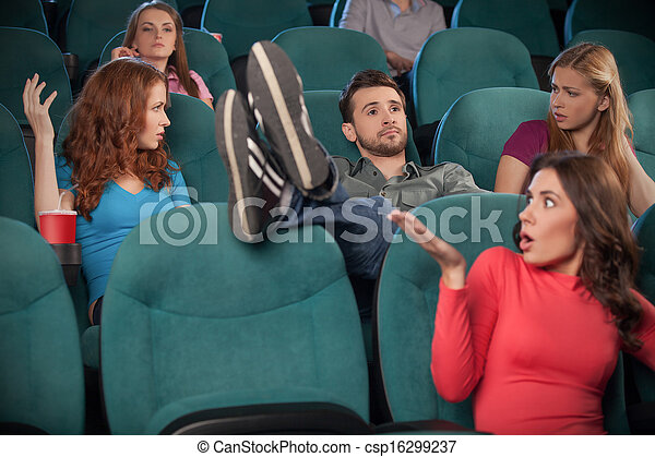 I don?t care about anyone. Young men holding his feet on the seat while watching movie at the cinema - csp16299237