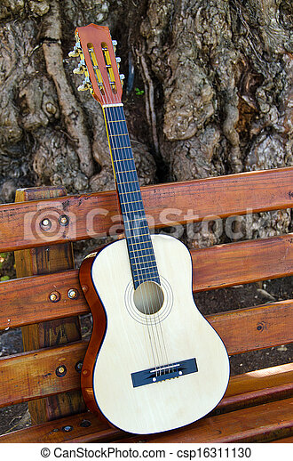 guitar on park bench - csp16311130
