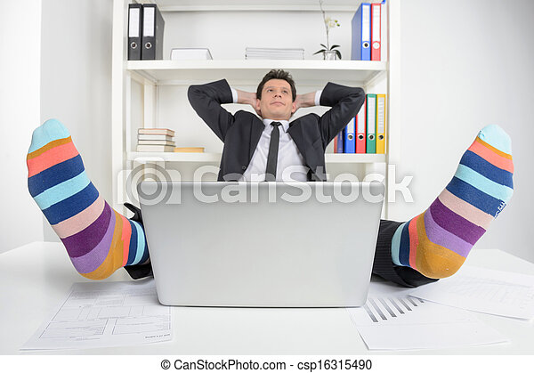 Funky socks. Happy businessman in funky socks sitting at his working place and holding head in hands - csp16315490