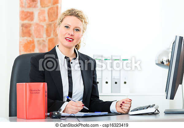 Lawyer in office with law book working on desk - csp16323419