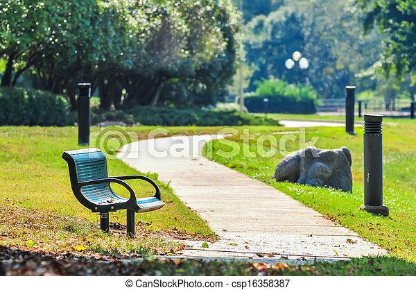 bench in a park with a walkway - csp16358387