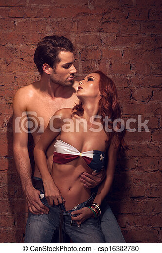 Couple of sexy models posing in fashion shoot. Looking into each other eyes with passion - csp16382780