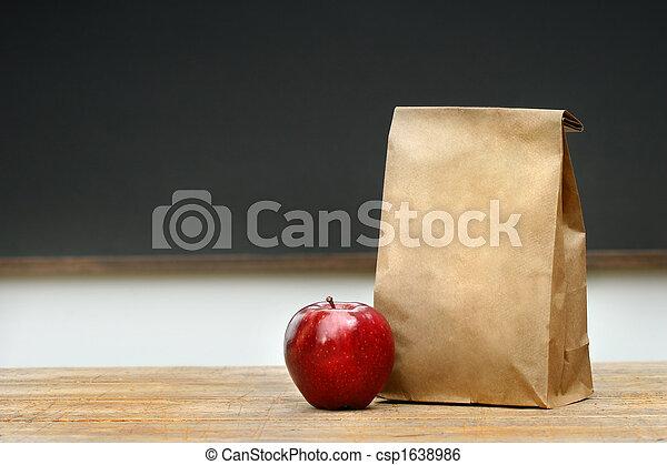 Paper lunch bag on desk  - csp1638986