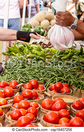 Customer paying for fresh organic vegetables on local farmers market