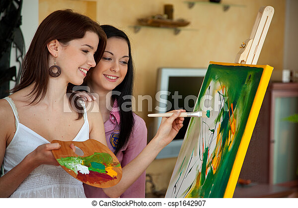 Young girl painting on an easel - csp1642907