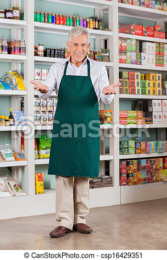 Senior Male Store Owner Welcoming In Supermarket