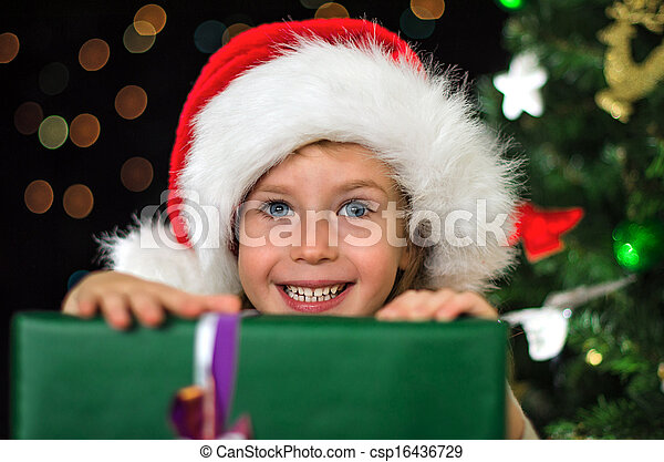 Little smiling girl with christmas gift.