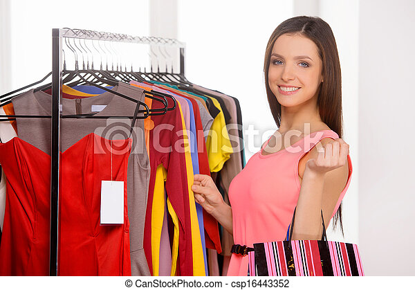 Woman shopping. Beautiful young woman choosing dress in retail store - csp16443352