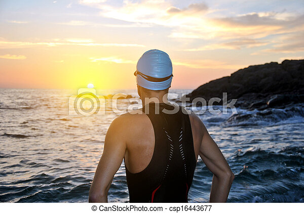 young athlete triathlon in front of a sunrise  - csp16443677