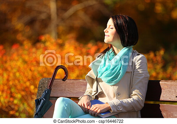Young girl relaxing in autumnal park. Fall lifestyle concept. - csp16446722