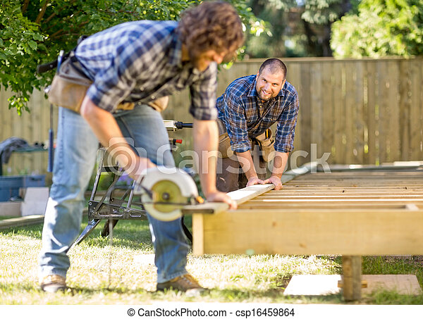 Mid adult carpenter looking at coworker while assisting him in cutting wood with handheld saw - csp16459864