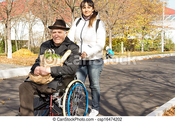 Woman helping her senior handicapped father pushing him along the street in his wheelchair as they return from doing his grocery shopping