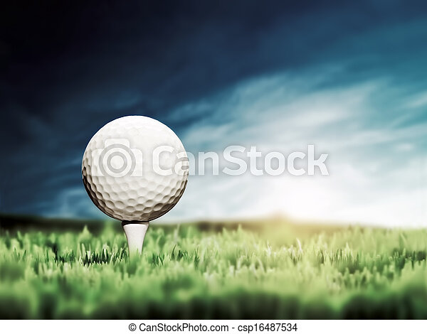 Golf ball placed on white golf tee on green grass golf course. Moody sunny sky.