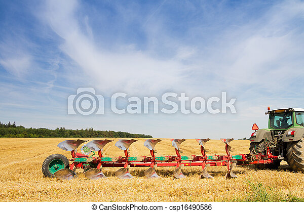 Agriculture tractor ready to plow stubble field - csp16490586