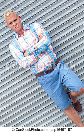 attractive young adult man with blue eyes standing outdoor - csp16497187