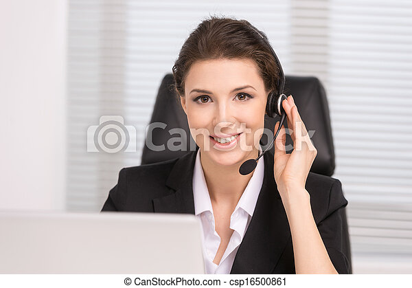 Customer service representative. Confident middle-aged woman in headphones sitting at her working place and smiling - csp16500861
