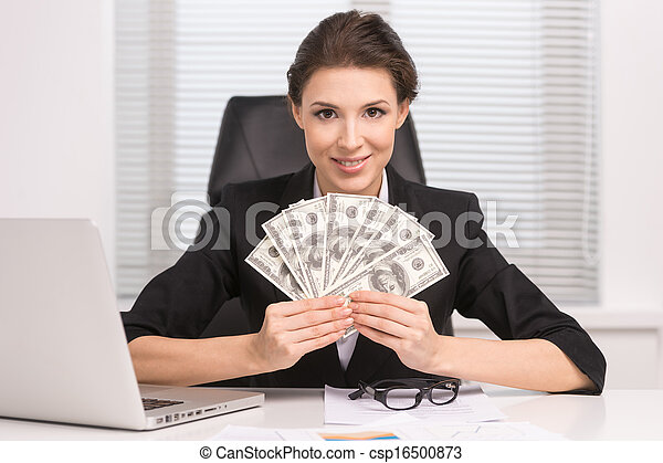 Successful businesswomen. Confident middle-aged woman sitting at her working place and holding money in her hands - csp16500873