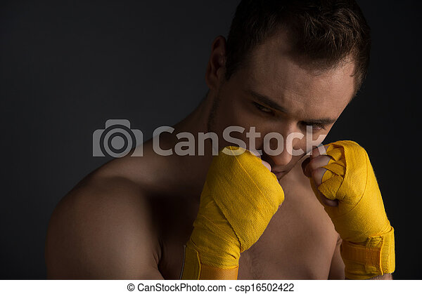 Close up of handsome young sportsman. Training martial arts, looking away