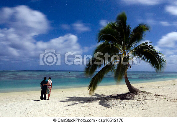 Young couple stand beside a coconut palm tree and watches the stars at night on deserted tropical island Aitutaki Lagoon, Cook Islands. Photo by Rafael Ben-Ari/Chameleons Eye