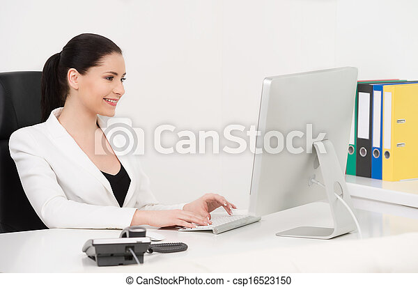 Businesswoman. Beautiful middle-aged businesswoman sitting at her working place and typing something on the computer - csp16523150