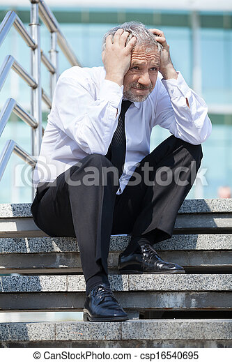 Depressed businessman. Depressed senior man in formalwear holding his head in hands while sitting on stairs
