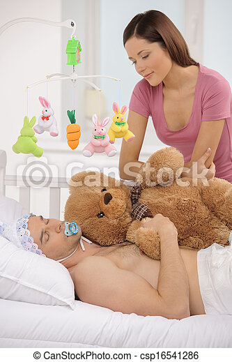 Big baby in bed. Infant adult man lying on the baby bed while young woman looking at him - csp16541286