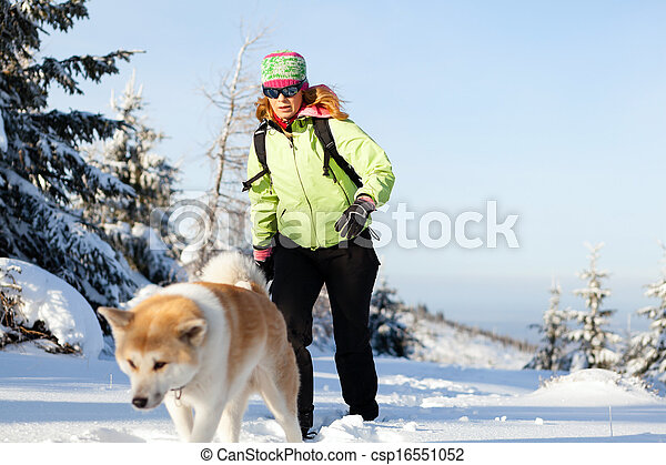 Woman winter hiking with dog - csp16551052