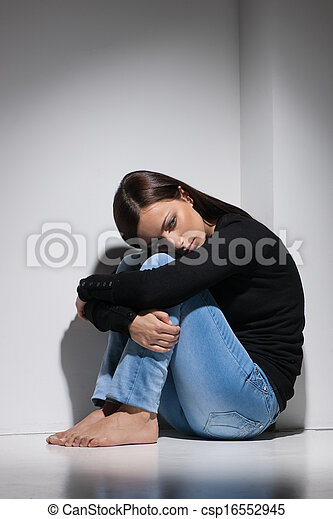 Depressed women. Young depressed women sitting on the floor and holding her head on knees - csp16552945