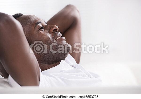 Men resting. Side view of happy African descent men sitting with his head in hands - csp16553738