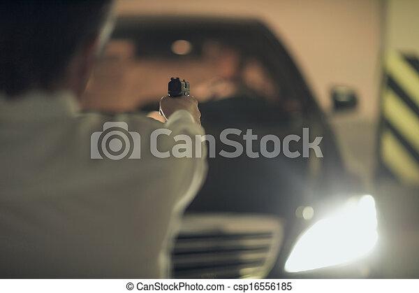 Killer with gun. Rear view of men with handgun aiming the car driver